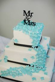 Black and white buttercream cake with cascading blue sugar flowers