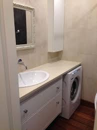 eine waschmaschine unter der arbeitsplatte im badezimmer