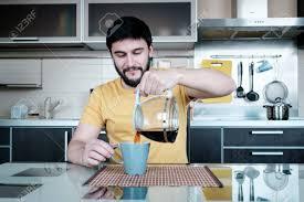lustige kochen attraktiver kaukasischer mann trinkt kaffee in der küche