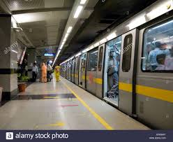 A yellow line train carriage with open doors at a platform on the