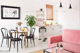 rosa sofa innen weiße apartment mit küchenzeile und schwarze stühle am esstisch echtes foto stockfoto und mehr bilder baum