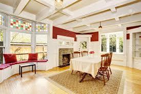 helles esszimmer in roten wänden und weißen holz drum und dran auch kamin mit steindekor und einer sitzecke mit breiten fenster