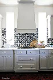 gray kitchen cabinets with black and white backsplash