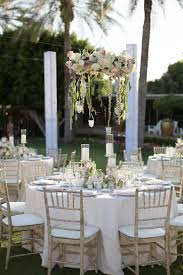 Garden Wedding Reception With Floral Chandeliers Tables In White Tablecloths And Weathered Chairs