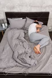 junge müde mann im pyjama schlafen ohne decke im stilvollen bett in grauen farben und in der nähe nachttisch mit kerzen in einem schlafzimmer im