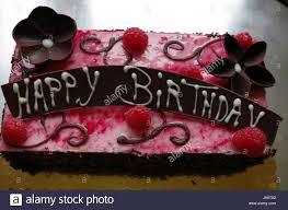 Chocolate birthday cake with chocolate flower and raspberry decorations and a chocolate HAPPY BIRTHDAY sign