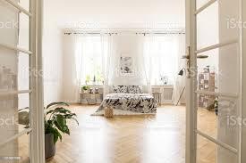 sonne durch die fenster in einen stilvollen schlafzimmer innenraum in einer villa shinning großes bett mit bettwäsche stehen auf fischgrätenparkett