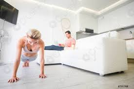 foto auf lager fitness gesundes mädchen zu hause im wohnzimmer für wellness lifestyle schieben während der freund am laptop computer auf dem sofa