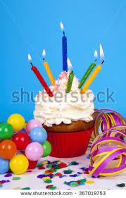 Birthday cupcake with lots of candles party streamers and colorful confetti over blue background