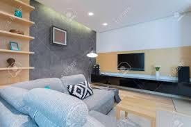 geräumiges wohnzimmer interieur mit sofa bücherregale couchtisch aus holz decken hintergrundbeleuchtung le und schwarz kommode