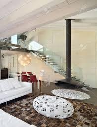 moderne wohnzimmer im dachgeschoss mit weißem ledersofa und kamin aus schwarzem eisen