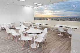 weiße holzstühle im esszimmer des modernen büros mit fenster und stadtansicht