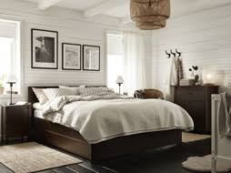 A Small Bedroom Furnished With Brown Bed Combined Chest Of Drawers And Bedside