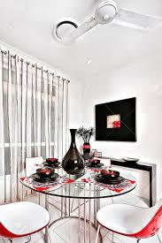 esszimmer eines luxuriösen haus sind stühle gebogen und in rot der runde tisch ist aus glas und es gibt eine glänzende schwarze vase mit tassen und