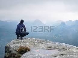 Adult Tourist In Black Trousers Jacket And Cap Sit On Cliffs Edge Looking To Misty