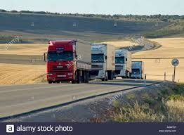 99 Y Trucks A Convoy Of Trucks On A Road Crossing A Plain In The Canton Of Stock