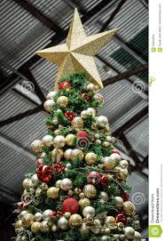 Large Artificial Christmas Tree In Warehouse Decorated With Red And Gold Sparkling Balls White Lights A Garland Glittering Star
