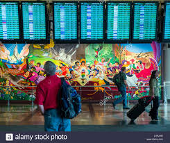 travelers pass colorful mural titled in peace harmony with