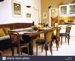 holztisch und stühlen und sitzbank in gelb esszimmer
