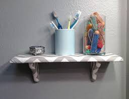 white wooden bathroom wall shelves above stainless steel grab bar