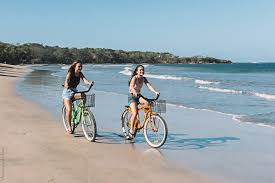 Two Teenage Girls Riding Bicycles On Beach By Preappy For Stocksy United