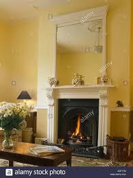 weißer spiegel über weißen kamin in pastell gelb wohnzimmer