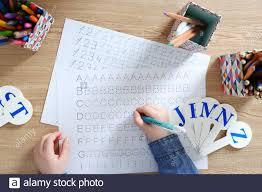 kleines mädchen das lernt englische buchstaben am tisch zu
