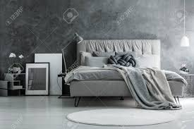 schlafzimmer im loft stil mit grauem design betonwand und modernen möbeln