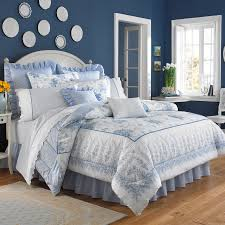 Charming Blue And Floral Laura Ashley Bedding With White Headboard Plus Pillows On Wooden Floor
