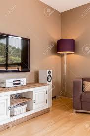 tv wohnzimmer in beige mit stehle sofa und weißer kommode