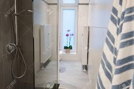 modernes hotel bad orchidee in der fensterbank mit der blüte gesehen hinter einer duschkabine aus glas und frische bettwäsche