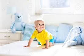 baby spielt auf bett der eltern nette lustige kleine junge lernen in weiß sonnigen kinderzimmer zu kriechen säuglings und kleinkindrauminnenraum