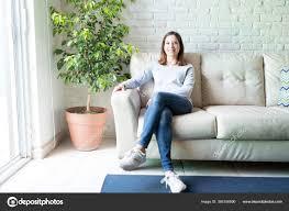 ganzkörperporträt einer frau die die hause wohnzimmer sitzt
