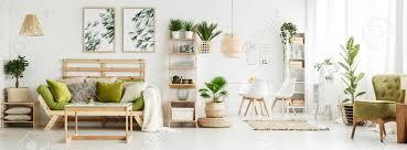 blätter poster auf weiße wand über grünem sofa mit kissen und decke in geräumigen wohnzimmer mit pflanzen