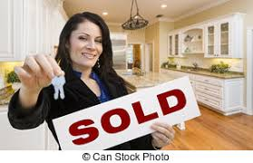 Hispanic Woman In Kitchen Holding House Keys And Sold Sign