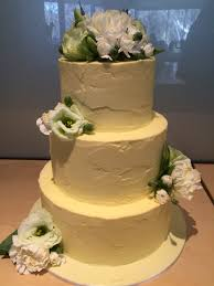 3 Tier Rustic Wedding Cake Covered In Rough Buttercream With Fresh Flowers