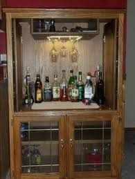 repurposed wardrobe armoire converted to a lighted dry bar by