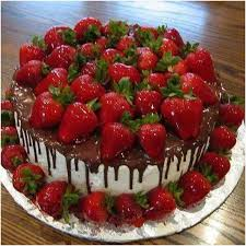 Chocolate cake with white chocolate icing drizzled with chocolate sauce and covered with fresh strawberries