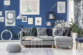 grauer puff auf teppich und len über grauer im wohnzimmer mit fahrrad gegen dunkelblaue wand mit galerie