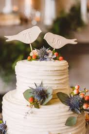 The Cake Was Decorated With Thistle Berries Eucalyptus And Bird Shaped Toppers