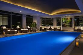 Nighttime View Of An Indoor Pool Overlooked By Lounge Chairs