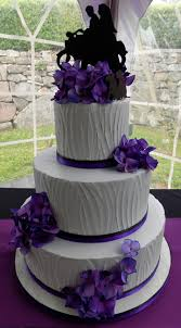 Three tier buttercream wedding cake iced with textured light grey vanilla buttercream and decorated with black and purples ribbons as well as silk purple