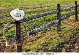 American West Rodeo Vintage Cowboy Hat And Authentic Lariat Lasso Hanging On A Ranch Fence Post
