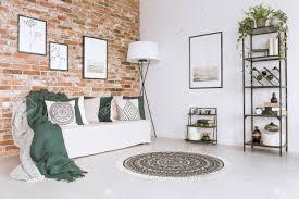 grüne decke auf weißem sofa und kissen im wohnzimmer mit gemustertem teppich le und einfachen postern