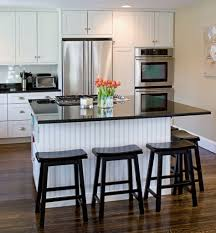 Kitchen With White Shaker Cabinets Beadboard Backing On Island Black Marble Countertop And
