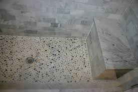pebble tile shower floor including white marble tile shower walls