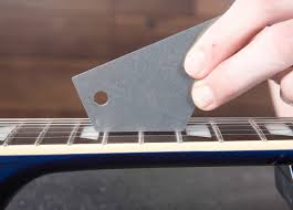 Fret Rocker Held On Top Of Guitar Frets