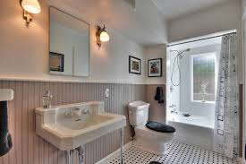 cottage bathroom with wall sconce limestone tile floors in