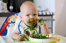 Feeding. Adorable Baby Child Eating With A Spoon In High Chair...