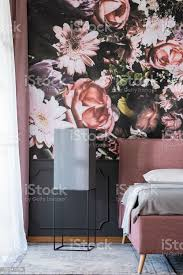 blumentapete im dunklen schlafzimmer innenraum mit schwarzen tisch neben rosa und grauen bett echtes foto stockfoto und mehr bilder bett